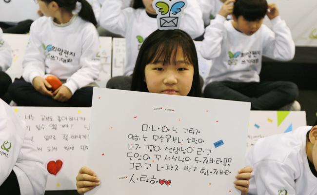 희망편지쓰기대회 발대식에 참여한 어린이가 희망편지를 판넬에 써서 카메라를 향해 들어보이고 있는 모습